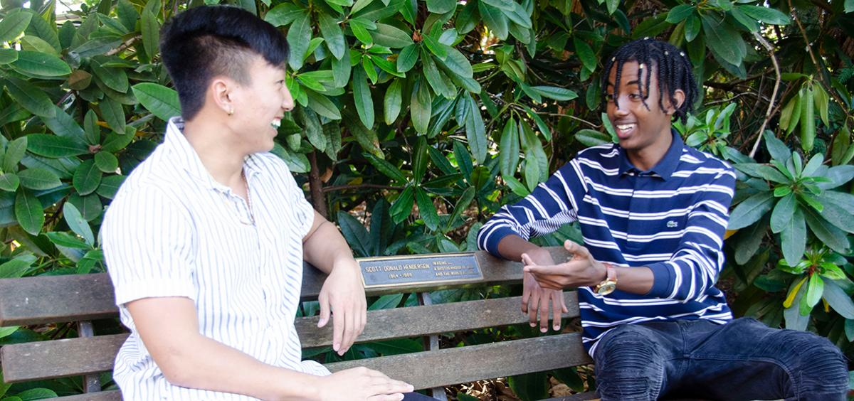 Two MDE students sitting on a bench talking